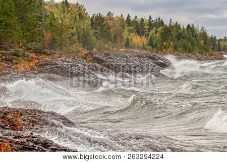 Big Waves On Rocky Shore Of Lake Superior Along Autumn Forest