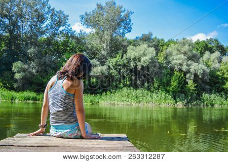 The Girl Sits On The River Dock, A Hot Summer Day, Rear View. Girl Sitting On Pier And Lookingat The