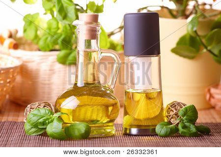 Two bottles with olive oil and grape seed oil with decoration of fresh basil