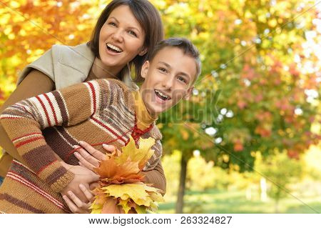 Portrait Of A Mother With Son Hugging Outoors In Autumnal Park