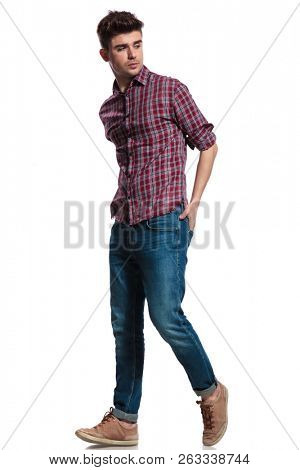side view of attractive casual man stepping to side while holding hands in pockets, full body picture