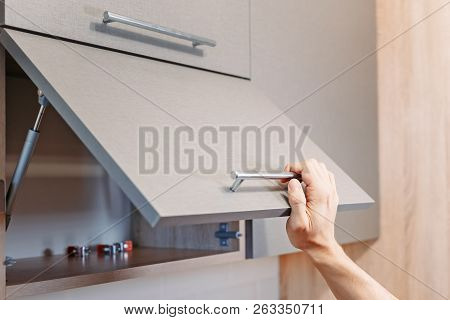 man hand open kitchen cupboard with handle, close up poster