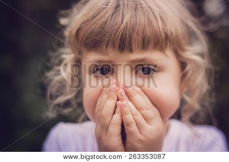 Little Girl Standing In The Park With Her Hands Covering Her Mouth Indicating She Is Scared Or Worri