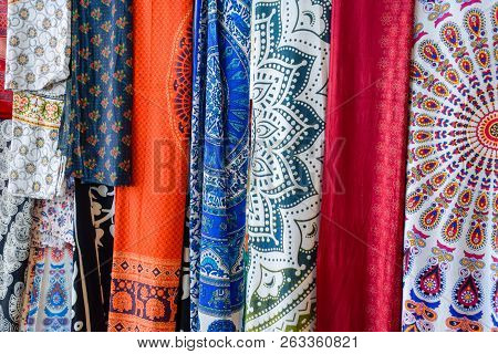 Indian Fabrics Hanging On The Counter. Trade In Fabrics From India. Fabric With Patterns And Pattern