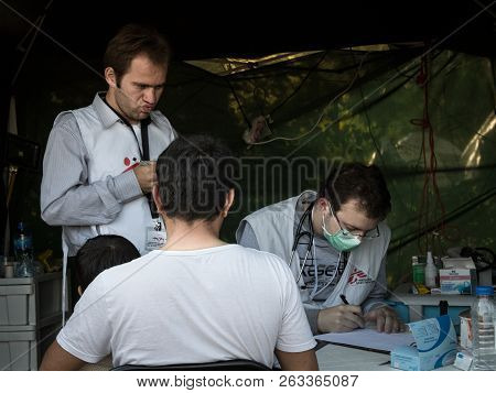 Berkasovo, Serbia - October 3, 2015: Medecins Sans Frontieres Doctors Discussing With A Refugees Fam