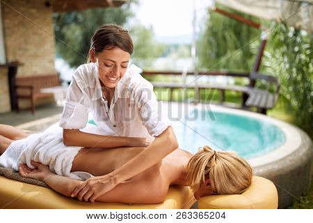 Smiling massage therapist doing a back massage on outdoor