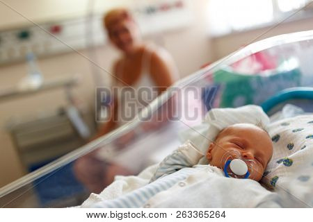 Beautiful newborn baby boy laying in crib in prenatal hospital