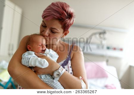 Mother kissing newborn son - Portrait of beautiful woman and little baby boy