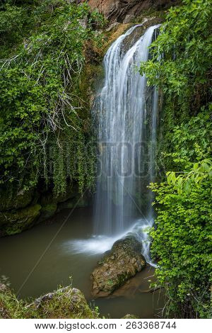Clean Cascade Water Flowing On Rock To Pond In Green Woods in Long Exposure