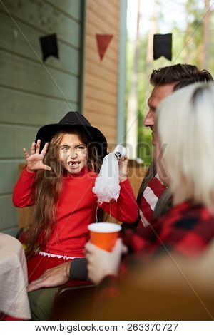 Adorable girl in halloween attire frightening her parents while sitting with them on terrace poster