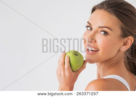 Beautiful woman with healthy white teeth holding green apple on white background