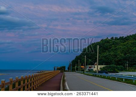 Empty Two Lane Country Road Along Oceanside Boardwalk Under Blue Sky With White And Pink Clouds At S