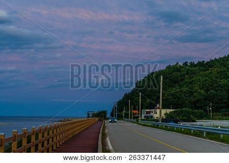 Car Traveling On Two Lane Country Road Along Oceanside Boardwalk Under Blue Sky With White And Pink