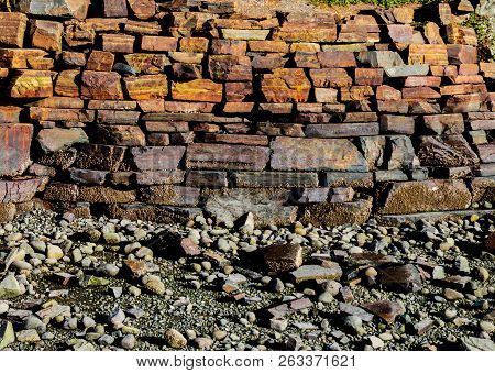 Stacked Iron Ore Stone Wall Along A Rocky Beach Shoreline