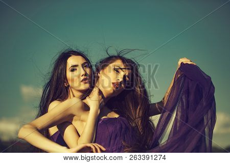 Young Pretty Women With Long Windy Hair In Elegant Violet Dresses Sunny Day Outdoor On Blue Sky Back