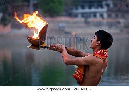 UJJAIN, INDIA - APRIL 23: Brahmin performing Aarti pooja ceremony on bank of river Kshipra on April 23, 2011 in Ujjain, Madhya Pradesh, India