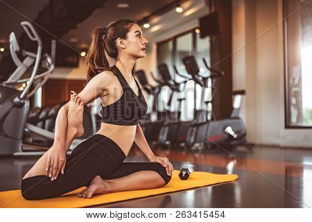 Woman Doing Bending Legs Yoga In Fitness Workouts Training Gym Center Background. Lifestyle Woman Si