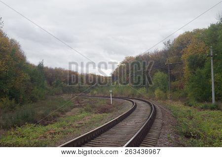 Autumn Railway Lines Stretching Beyond The Horizon. Overcast October Industrial Landscape Under Heav