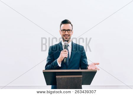 Smiling Speaker Gesturing And Talking Into Microphone At Podium Tribune During Seminar In Conference