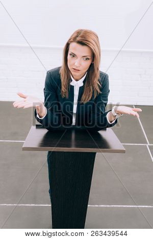 High Angle View Of Attractive Lecturer Standing At Podium Tribune And Showing Shrug Gesture In Confe