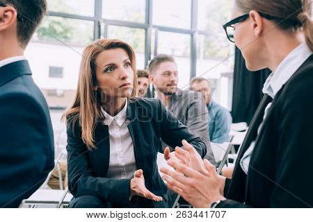 Attractive Businesswomen Sitting On Chairs And Talking In Conference Hall