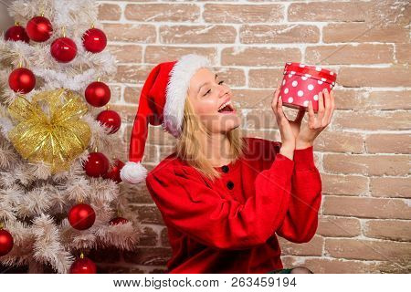 Girl Dress Near Christmas Tree. Woman In Santa Hat Hold Gift Box. Girl Celebrate Near Christmas Tree