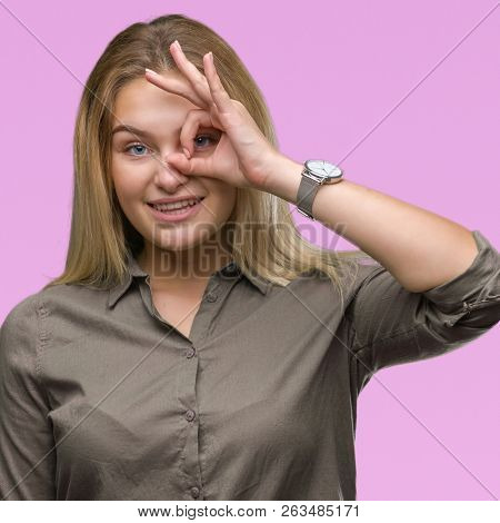 Young caucasian business woman over isolated background doing ok gesture with hand smiling, eye looking through fingers with happy face.