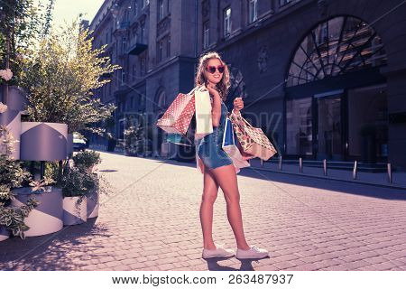 Contended Shopaholic Standing Near Fancy Boutique With Shopping Bags