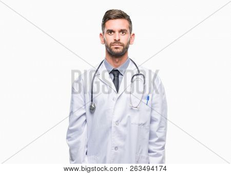 Young handsome doctor man over isolated background with serious expression on face. Simple and natural looking at the camera.