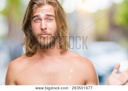 Young handsome shirtless man with long hair showing sexy body over isolated background clueless and confused expression with arms and hands raised. Doubt concept.