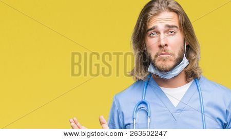 Young handsome doctor man with long hair over isolated background clueless and confused expression with arms and hands raised. Doubt concept.