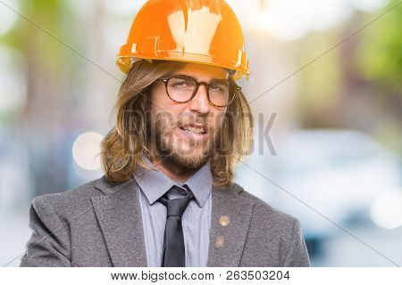 Young handsome architec man with long hair wearing safety helmet over isolated background disgusted expression, displeased and fearful doing disgust face because aversion reaction. With hands raised.