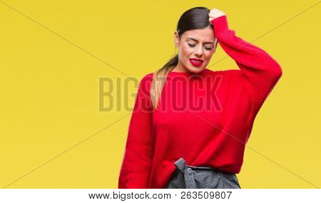 Young beautiful business woman wearing winter sweater over isolated background confuse and wonder about question. Uncertain with doubt, thinking with hand on head. Pensive concept.