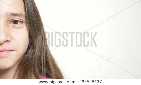 A Young Cheerful Girl Looks At The Camera. Close-up Half Face, Close-up. Space For Copying