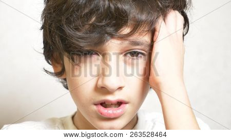 A Young Boy Looks At The Camera And Smiling. The Boy Laid His Head On His Palm And Looked Into The C