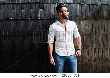 Stylish Tall Arabian Man Model In White Shirt, Jeans And Sunglasses Posed Against Wooden Wall Indoor