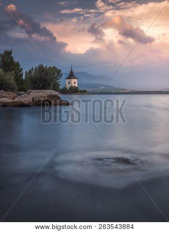 Church By Liptovska Mara Lake With Western Tatras Mountains At Sunset In Slovakia