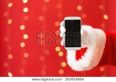 Santa Holding A Smartphone On A Shiny Light Red Background