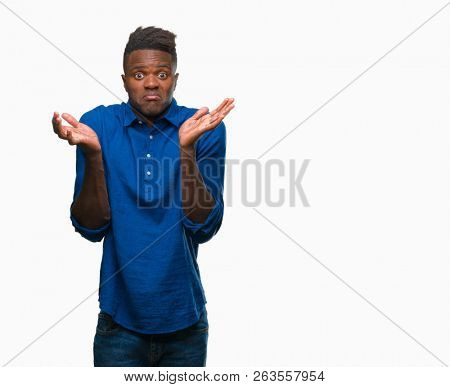 Young african american man over isolated background clueless and confused expression with arms and hands raised. Doubt concept.