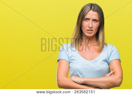Young beautiful woman over isolated background skeptic and nervous, disapproving expression on face with crossed arms. Negative person. poster