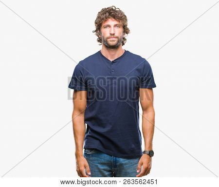 Handsome hispanic model man over isolated background with serious expression on face. Simple and natural looking at the camera.