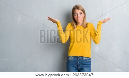 Beautiful young woman standing over grunge grey wall clueless and confused expression with arms and hands raised. Doubt concept.