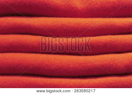 Stack Of Red Woolen Knitted Sweaters Close-up, Texture, Background