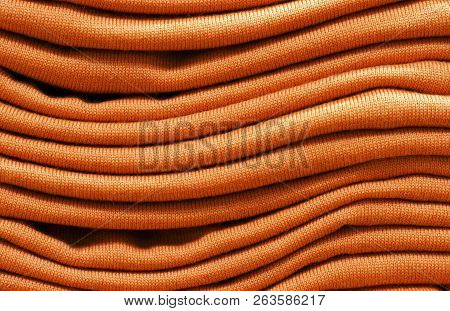 Stack Of Russet Orange Woolen Knitted Sweaters Close-up, Texture, Background