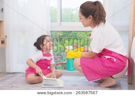 Asian Mother Teaching Daughter Cleaning Their Home . Family Housework Concept.