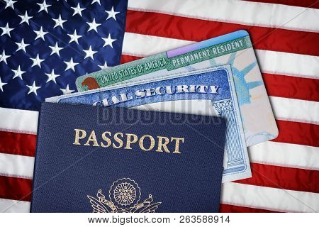 United States Passport, Social Security Card And Resident Card Over American Flag. Immigration Conce