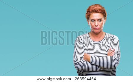 Atrractive senior caucasian redhead woman over isolated background skeptic and nervous, disapproving expression on face with crossed arms. Negative person. poster