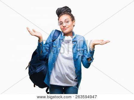Young braided hair african american student girl wearing backpack over isolated background clueless and confused expression with arms and hands raised. Doubt concept.