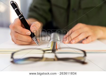 Woman's Hands With Pen Writing On Notebook. Modern Office Desk. Working, Writing Concept