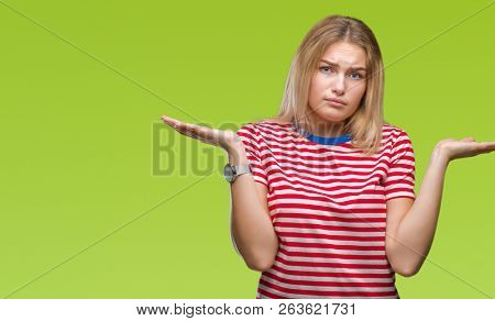 Young caucasian woman over isolated background clueless and confused expression with arms and hands raised. Doubt concept.